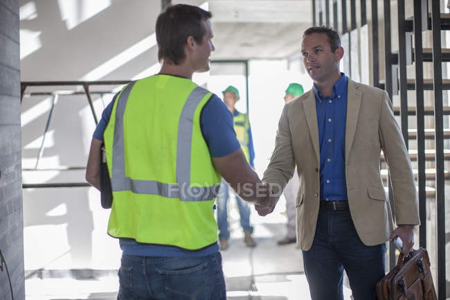 Two men shaking hands on construction site — Stock Photo