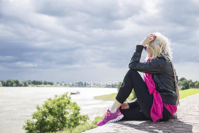 Женщина, сидящая на стене, на берегу Рейна — стоковое фото