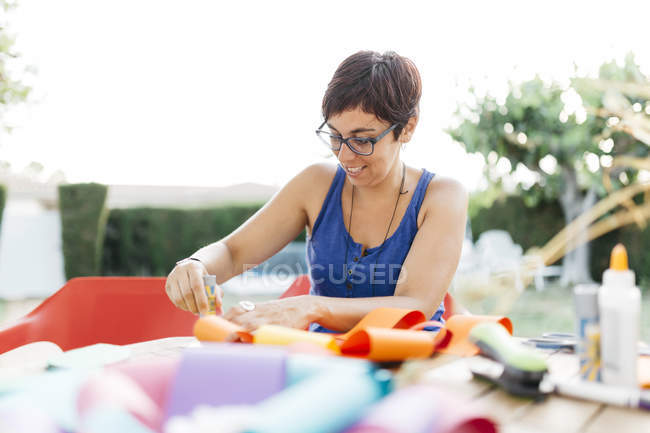Woman doing handicrafts at garden table — Stock Photo
