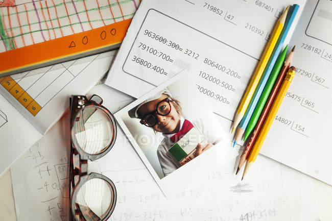 Портрет умного ребенка с книгами, очками, карандашами и записками — стоковое фото