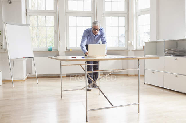 Empresario usando laptop - foto de stock