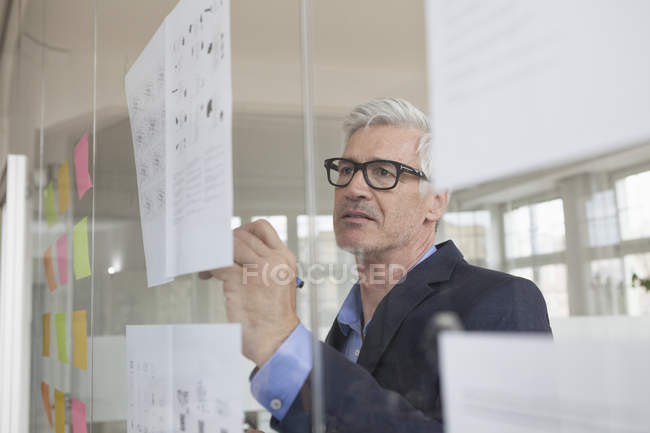 Businessman writing on paper at glass pane — Stock Photo
