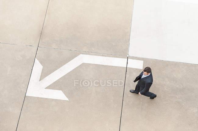 Бизнесмен идет по тротуару — стоковое фото