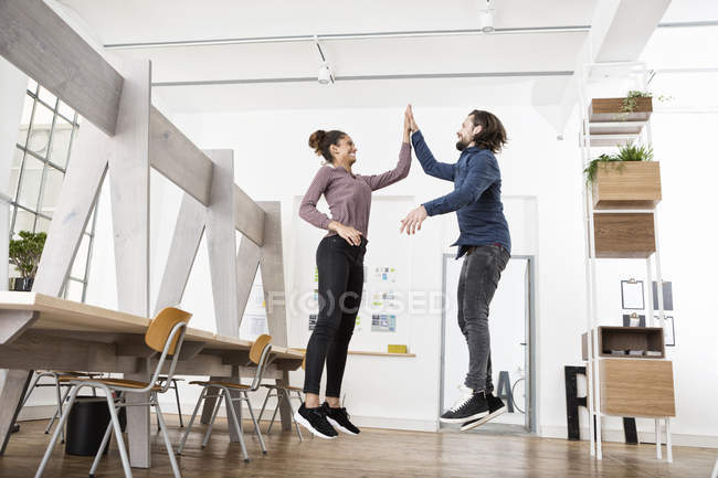 Two happy colleagues in office jumping and high fiving — Stock Photo