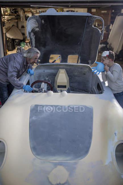 Hombre y muchacho trabajando en coche antiguo - foto de stock