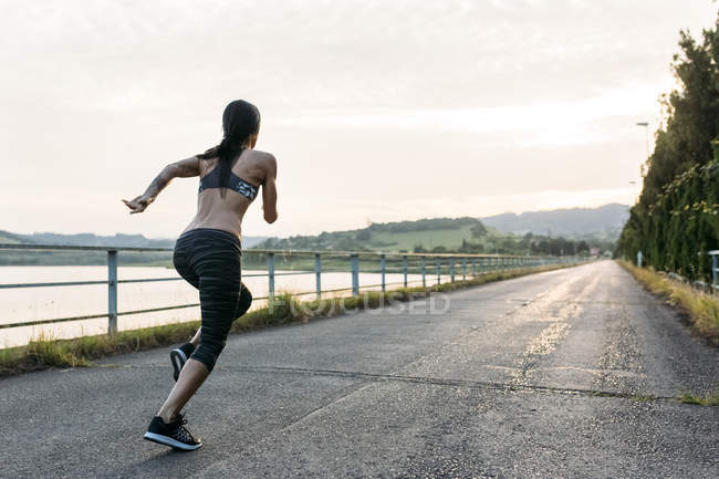 Back view of young Woman running outdoors — Stock Photo