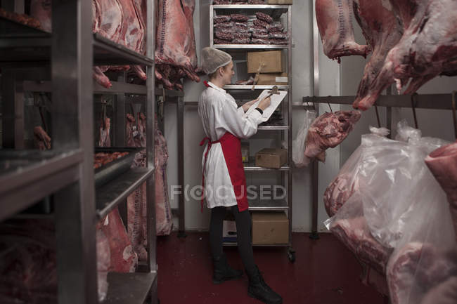 Woman with clipboard in butchery cold store — Stock Photo