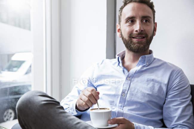 Giovane con tazza di caffè alla finestra — Foto stock