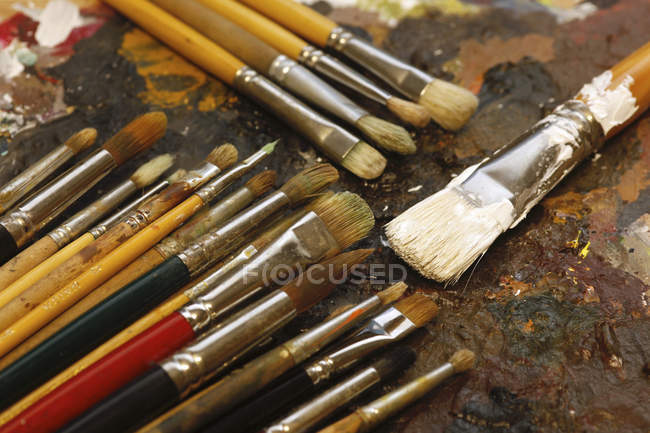 Different paintbrushes on artist's palette — Stock Photo