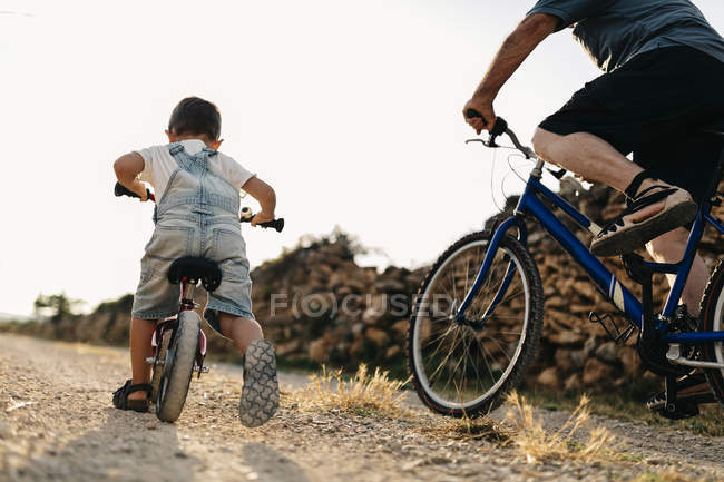 Little boy and great-grandfather on bicycle tour on dirt track — Stock Photo