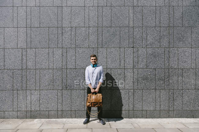 Businessman standing in front of a grey — Stock Photo