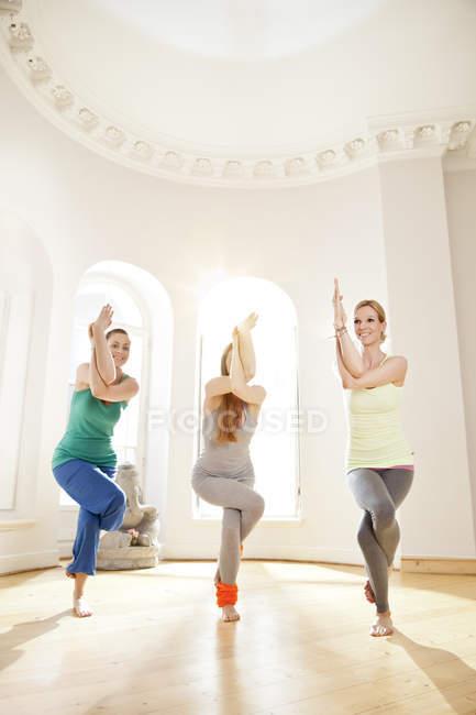 Три жінки в Сонячний йога студії проведення кручений позу — стокове фото