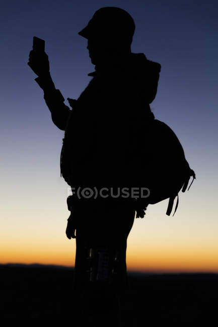 Silhouette of hiker looking at smartphone at sunset — Stock Photo