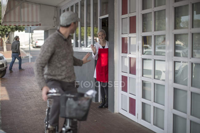 Shop assistant waving at man on bicycle outside shop — Stock Photo
