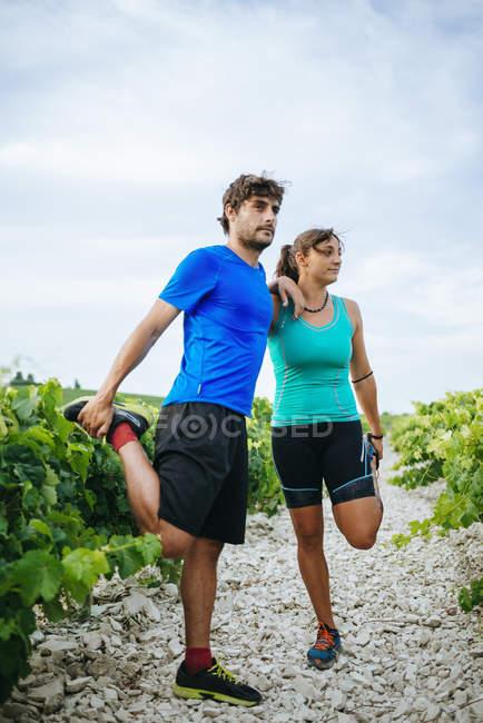 Couple faisant du sport dans un vignoble — Photo de stock
