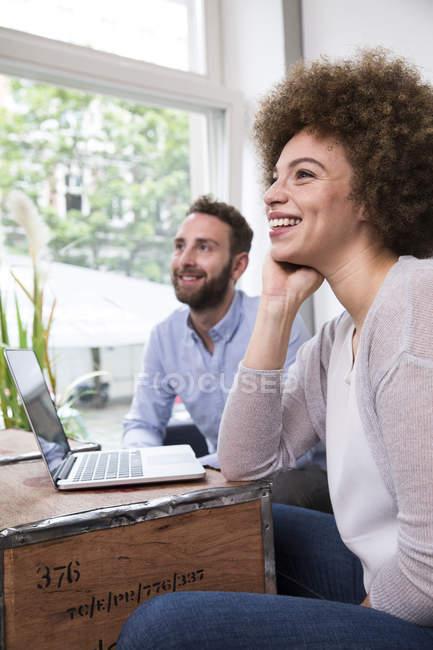 Молодая женщина и мужчина с ноутбуком у окна — стоковое фото