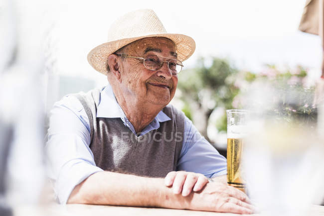 Portrait of happy senior man drinking glass of beer in a sidewalk cafe — Stock Photo