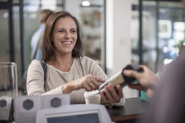 Cliente che paga senza contanti per il caffè da asporto — Foto stock