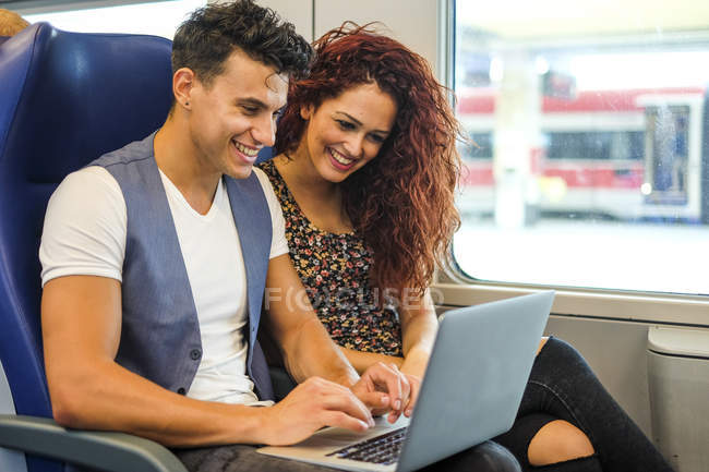 Smiling young couple in a train using laptop — Stock Photo