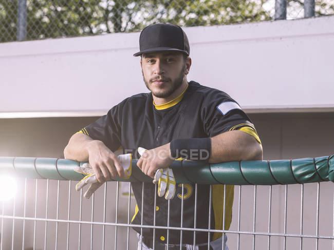 Portrait de joueur de baseball derrière une clôture — Photo de stock