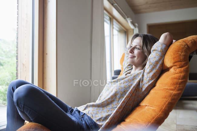 Улыбающаяся женщина отдыхает в кресле — стоковое фото