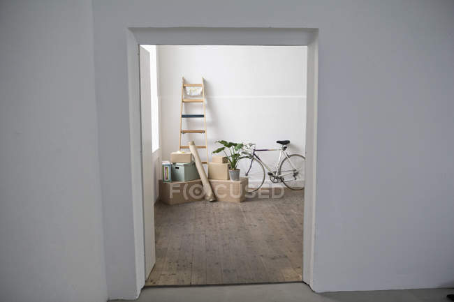 Daytime view through door of cardboard boxes and ladder — Stock Photo