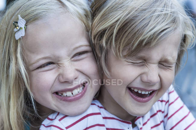 Retrato do garotinho rindo e sua irmã cabeça a cabeça — Fotografia de Stock