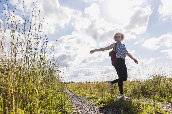 Happy young woman on field path — Stock Photo