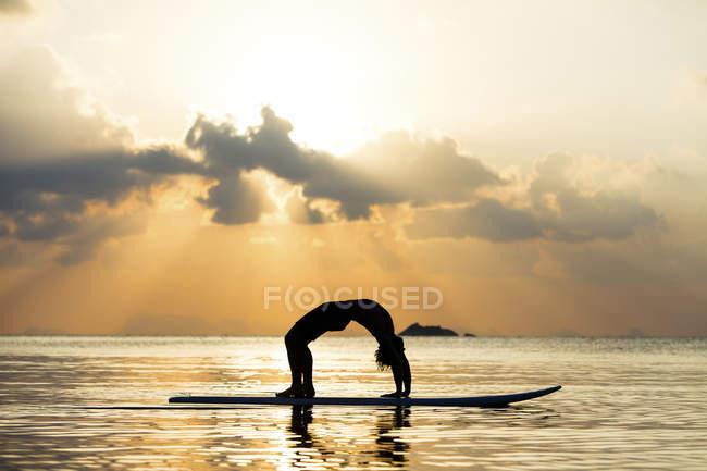 Thailand, mann macht yoga auf paddleboard bei untergang, Brückenposition — Stockfoto