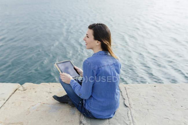 Jovem mulher sentada na doca usando tablet digital — Fotografia de Stock