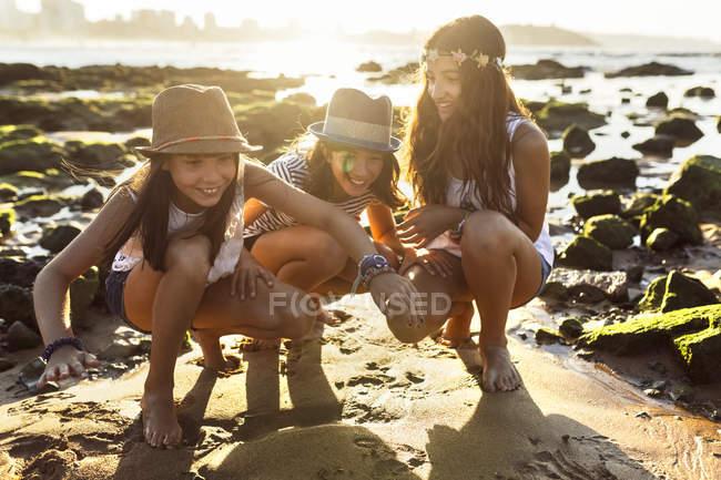 Tre ragazze felici sulla spiaggia al tramonto — Foto stock