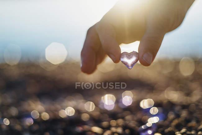 Человек держит стеклянное сердце — стоковое фото