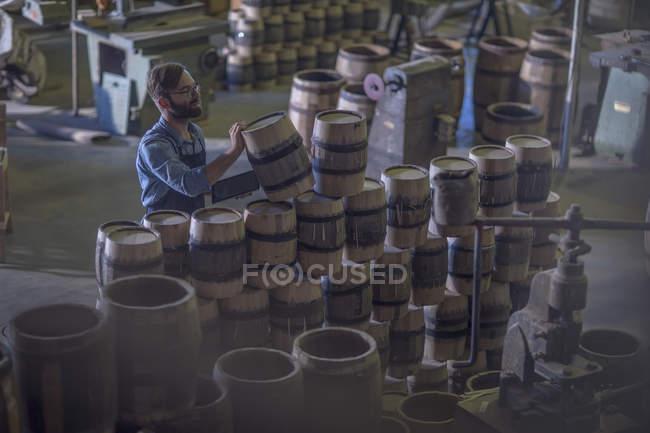 Macho cooper empilhando barris de vinho — Fotografia de Stock