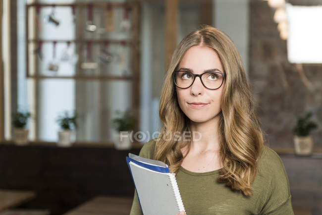 Portrait of sceptical blond woman with notebook in a coffee shop — Stock Photo