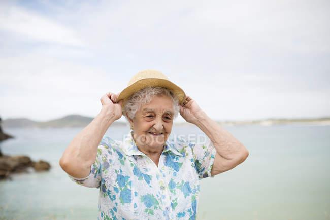Senior woman putting on straw hat — Stock Photo