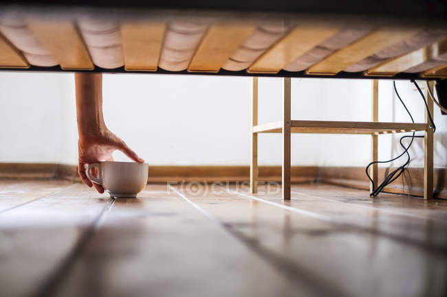 Womans main tenant la tasse sous lit — Photo de stock