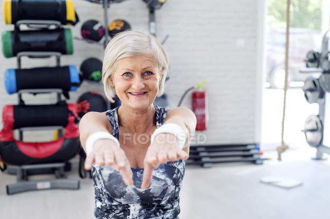 Smiling mature woman doing gymnastics — Stock Photo