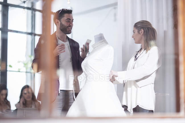 Two dressmakers with wedding dress discussing — Stock Photo