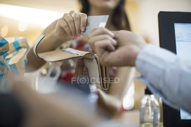 Woman paying with credit card in a shop — Stock Photo