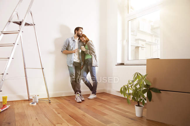 Smiling young couple having a coffee break in new apartment — Stock Photo