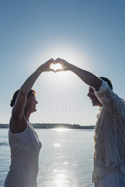 Couple standing at Lake Cospuden, forming heart with hands against the sun — Stock Photo