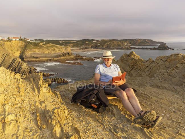 Livro de leitura homem sênior na praia — Fotografia de Stock