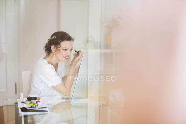 Smiling Woman applying mascara at home — Stock Photo