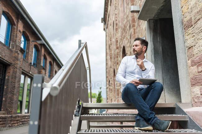 Бизнесмен с планшета, сидя на лестнице — стоковое фото