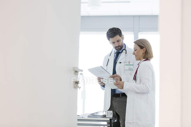 Two doctors discussing in office looking at papers — Stock Photo