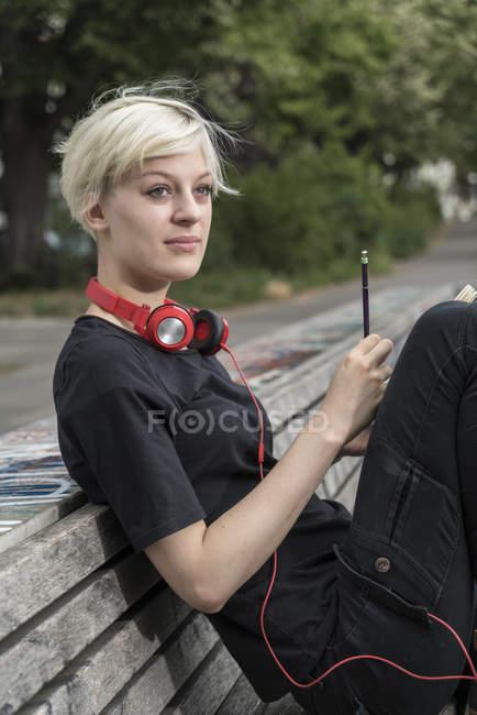 Ritratto di giovane donna con cuffie che disegna sulla panchina del parco — Foto stock