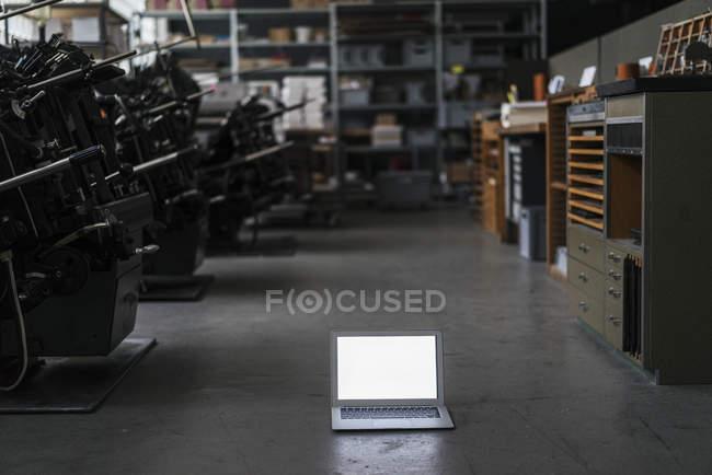 Ordenador portátil en el suelo en tipografía - foto de stock