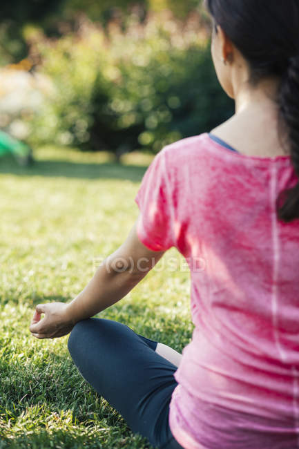 Back view  of Young woman meditating in park — Stock Photo