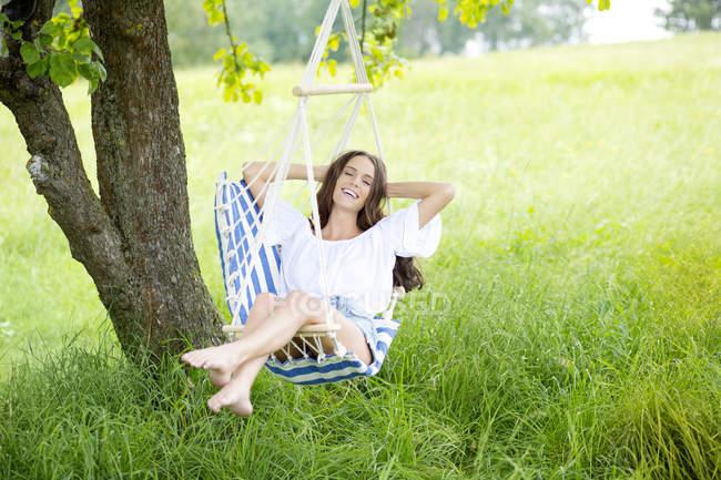 Щасливі жінка розслабляючий висячі стільці — стокове фото