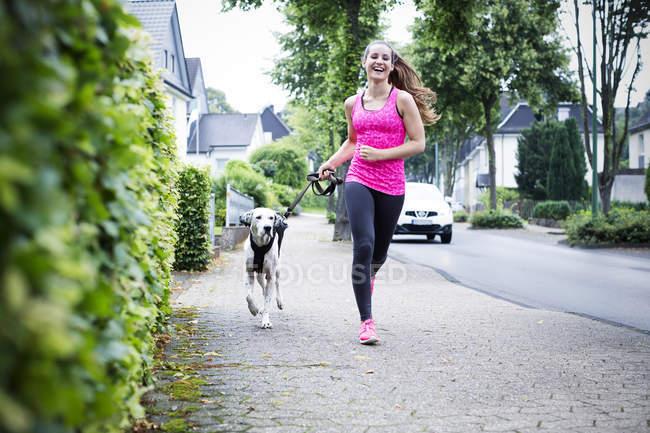Joven mujer corriendo con el perro - foto de stock